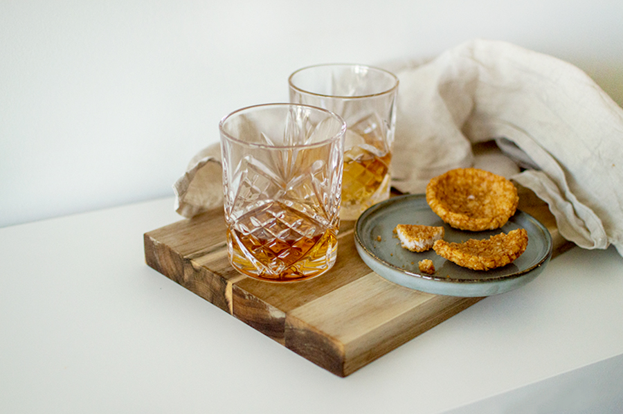 scandi lover gift guide with whisky glasses on natural wood chopping board